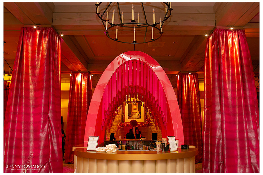 A classy beverage bar lined with pink curtains and covered by a decadent hot pink arch.