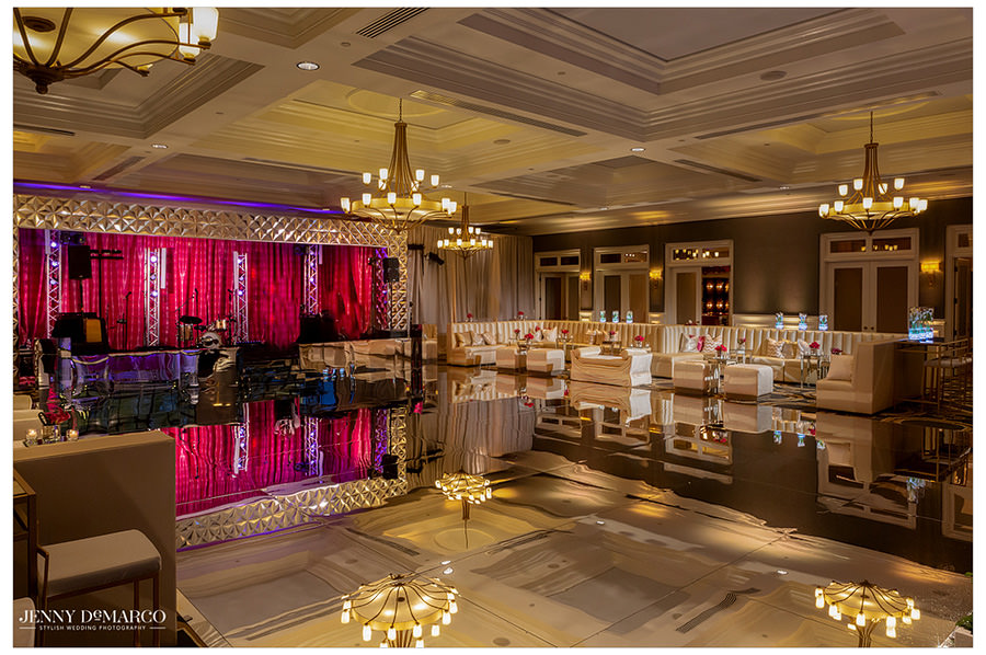 The ballroom at the reception space is decorated extravagantly with pink and white tones.