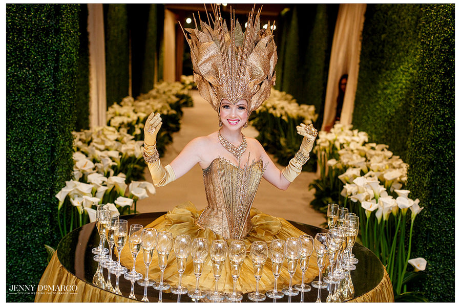 An extravagant girl's golden dress acts as a table as she hands out champagne to incoming guests.