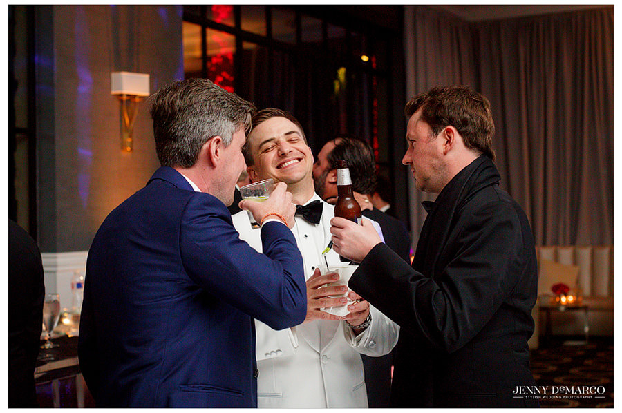 Groom laughs as he is entertained by two of his guests.