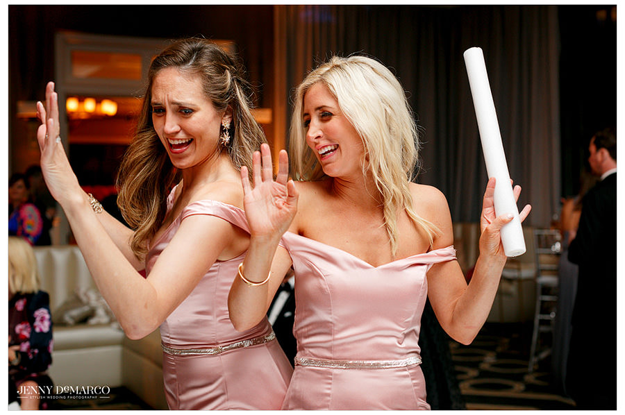 Two bridesmaids dance back-to-back in their pink gowns.