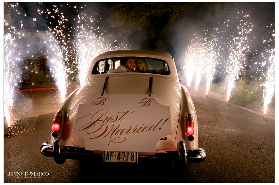 Bride and Groom leave in a classic white car on a road lined with sparklers.