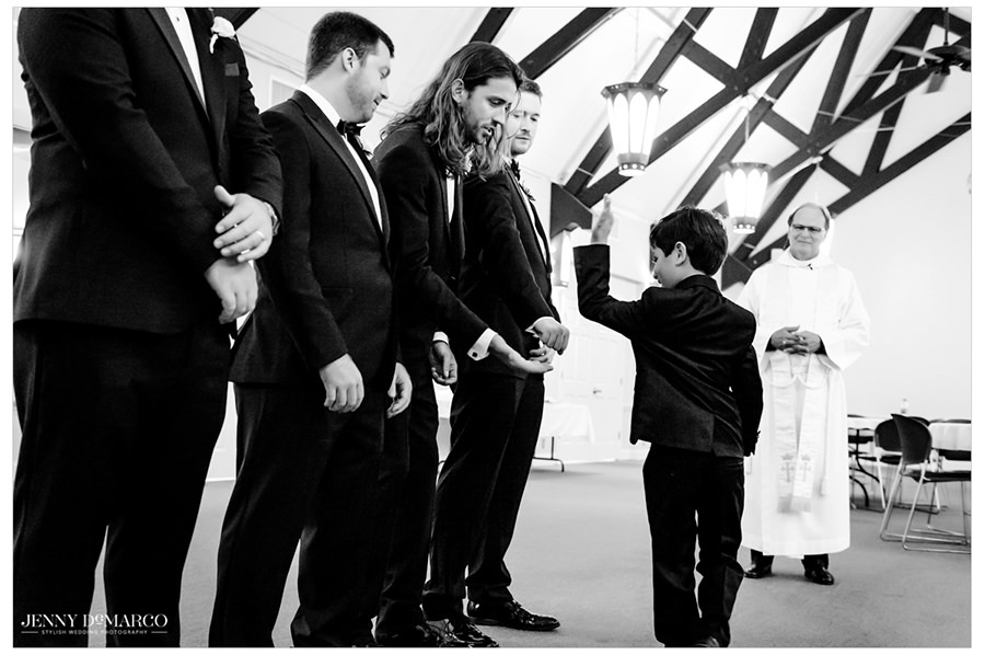 Ring bearer gives high fives to all the groomsmen as they wait for the ceremony to start.