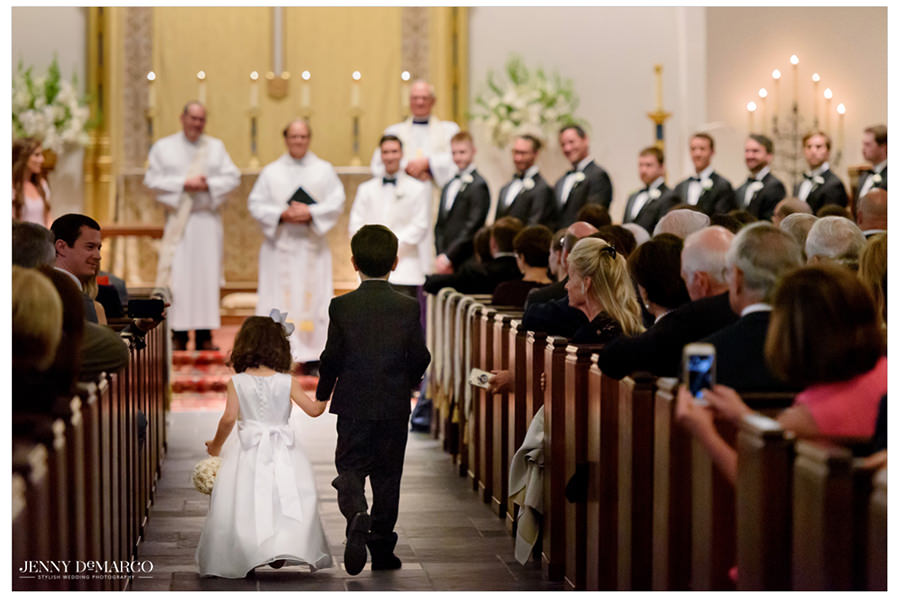 Ring bearer and flower girl start the ceremony by walking down the aisle hand in hand.