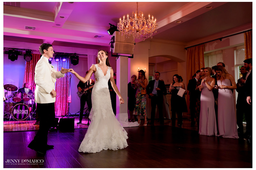The couple twirls as guests watch them dance on the dance floor.