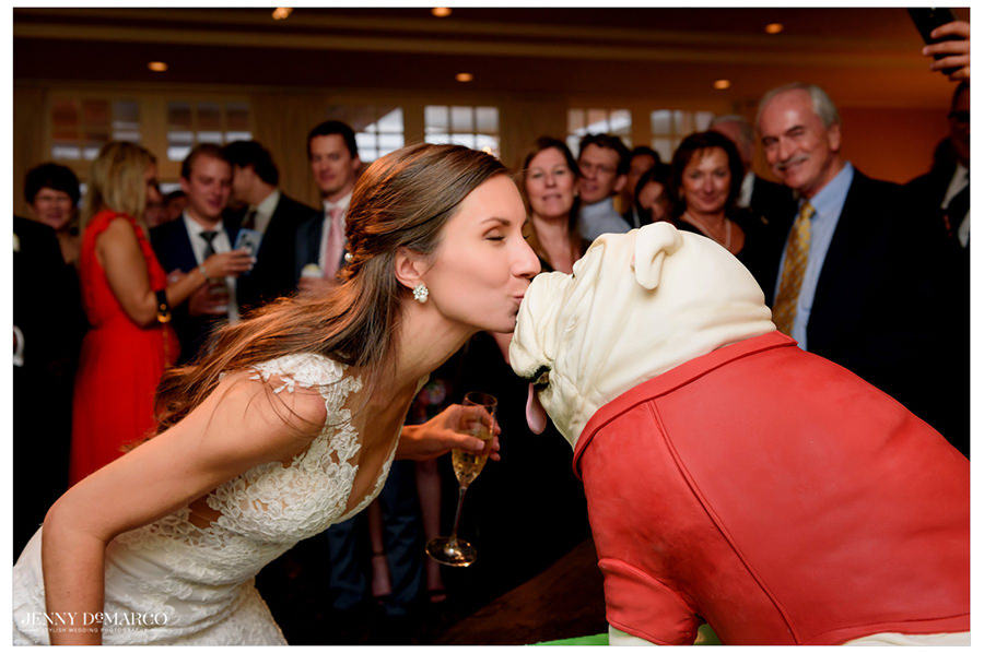 Bride gives the bulldog a kiss on the nose.