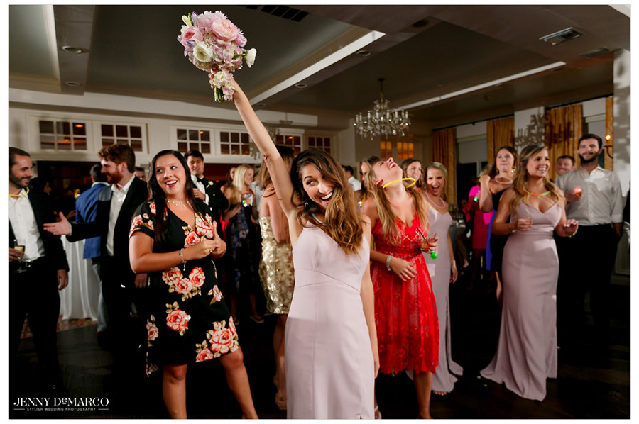 A candid photo of one of the bridesmaids catching the bride's bouquet.