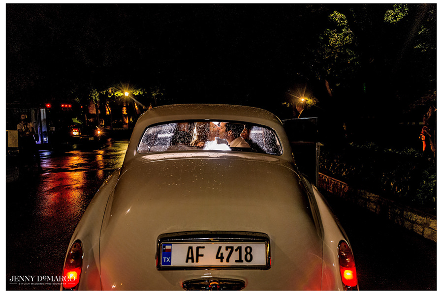 The couple share one last kiss as they head out in a vintage white car.