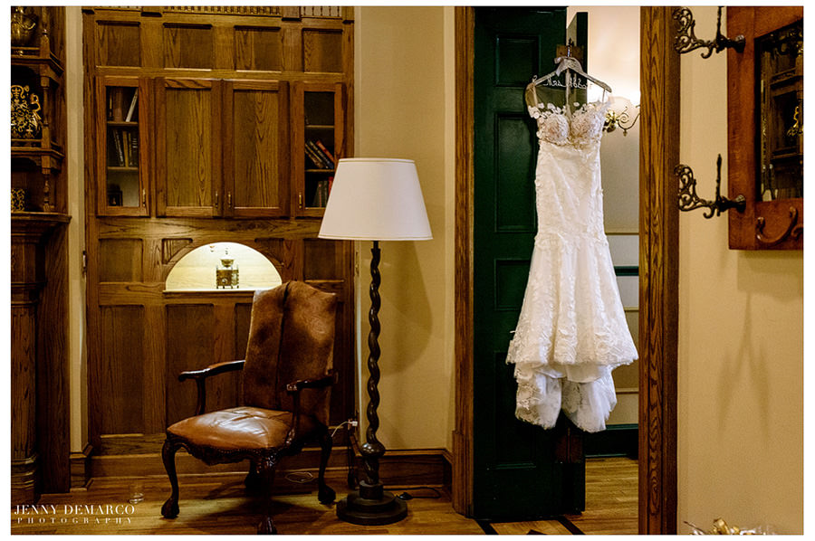 The bride's white lace wedding dress hangs from the door.