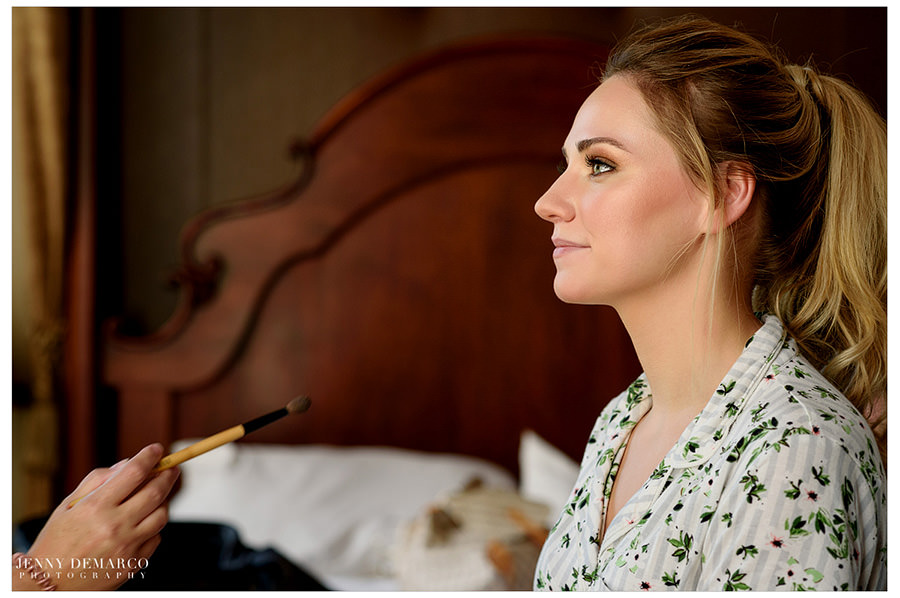 Bride gets her finishing touches on her makeup.