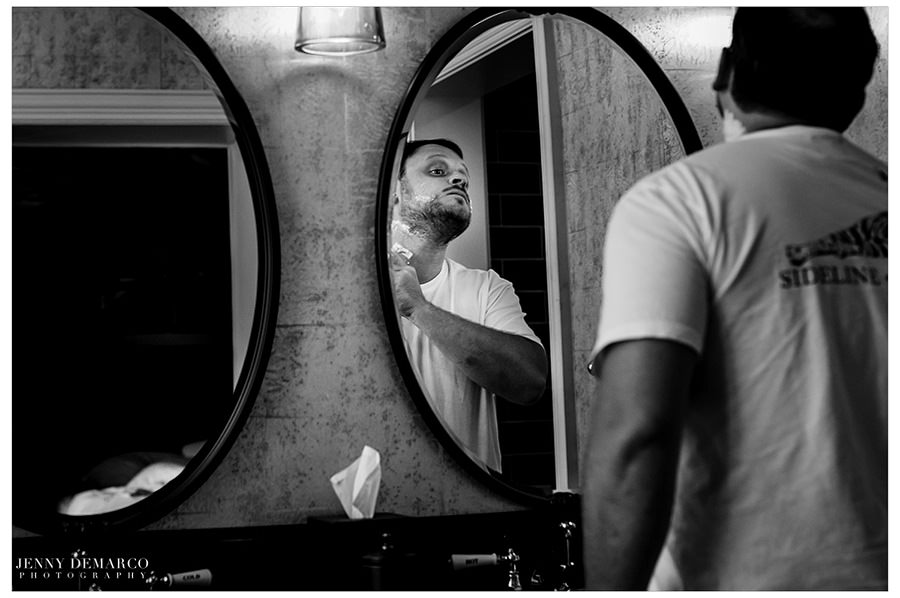 Groom gets ready by shaving his face.