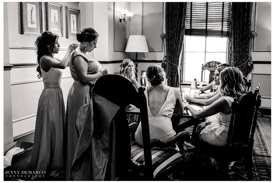 The bride sits at a table with her bridesmaids as they relax before the ceremony.
