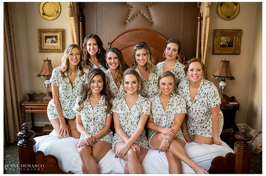 The bridal party is matching in white and green outfits.