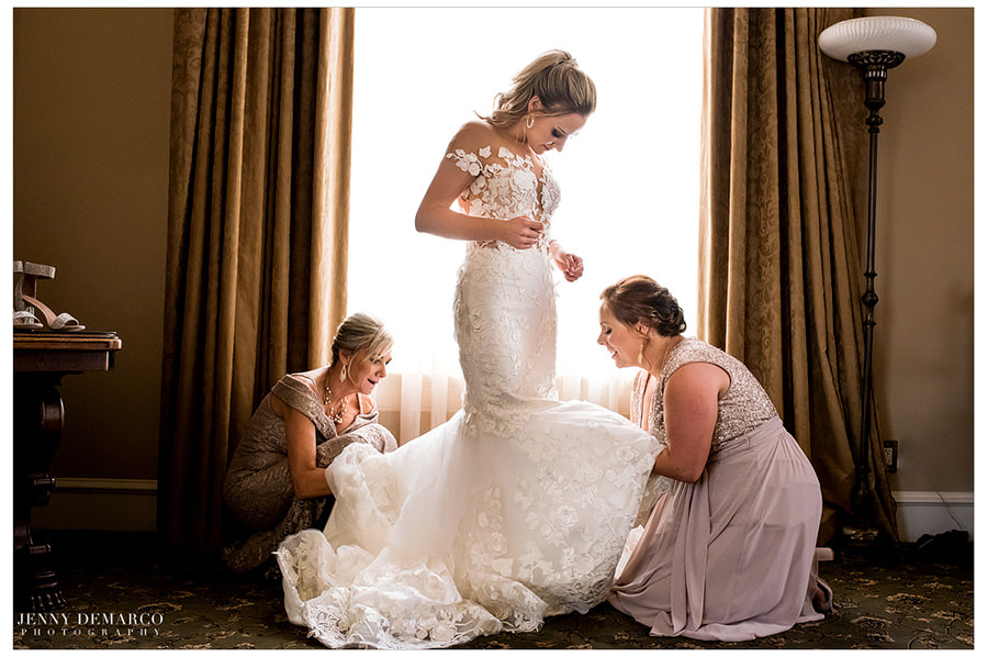 Mom and sister help the bride into her lace wedding dress.