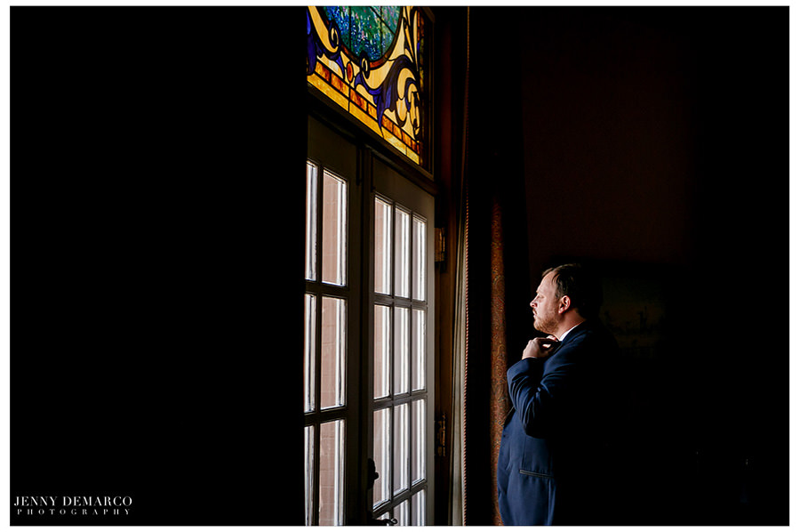 A moody photo of the groom looking longingly out a window as he anticipates the big day.