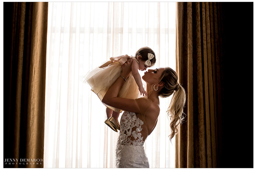 Bride holds the little girl in the air and gives her a kiss.