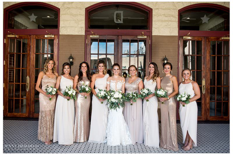 Bride poses with all of her bridesmaids for a group photo.
