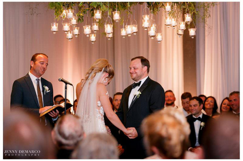 Bride and groom share a laugh as they stand in front of all their guests