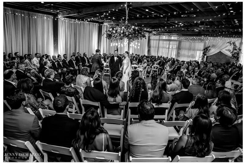 A wide angle black and white photo of all of the guests watching the ceremony.