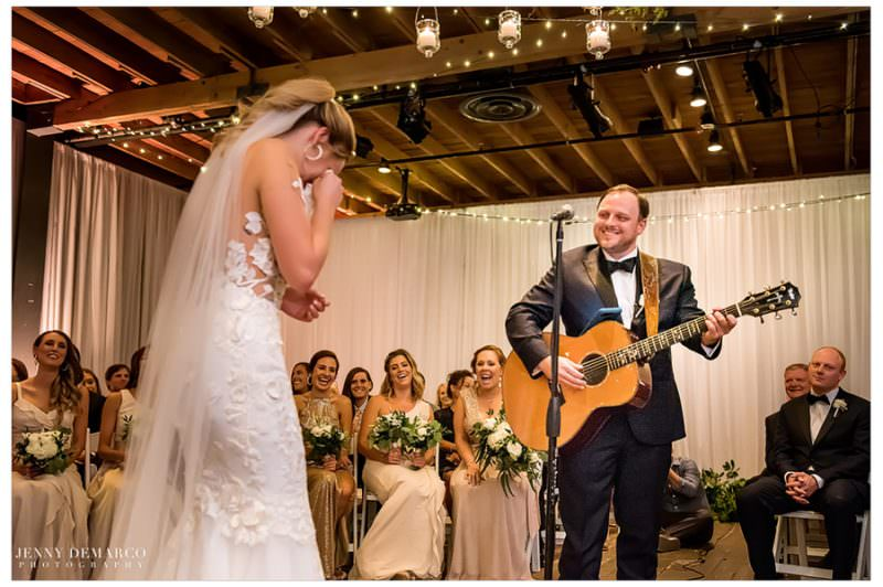 Josh serenades his bride with a guitar in the middle of ceremony.