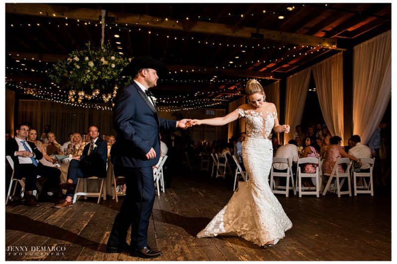 The newly weds have their first dance in front of all of their guests.