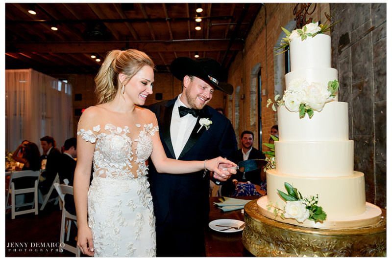 The newly weds join hands to cut their wedding cake.