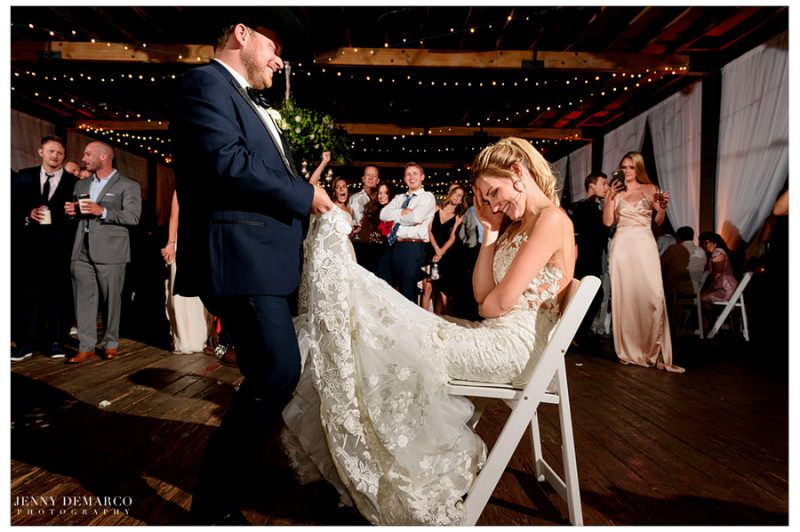 Bride closes her eyes and laughs as Josh begins to remove her garter.