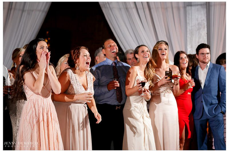 Guests excitedly cheer on the couple during the garter removal.