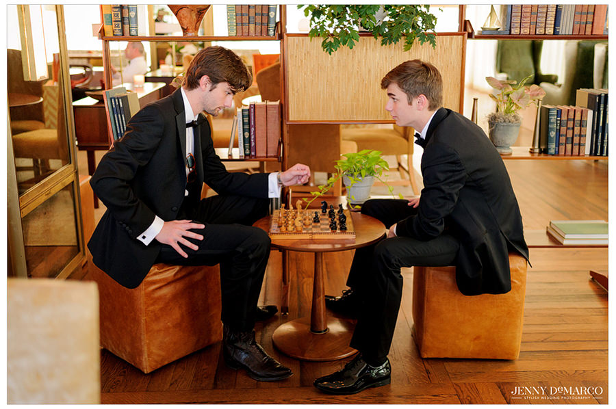 Two groomsmen pass the time by paying a game of chess.