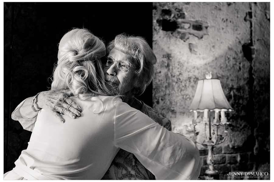 Bride gives a warm hug to her grandma in this black and white photo.
