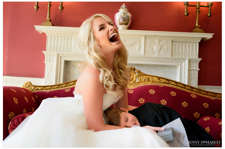 Elaine laughs with her new son as she gives him a gift and he lays on her lap.