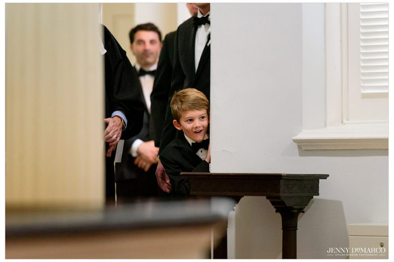 The little boy peaks his head into the church.