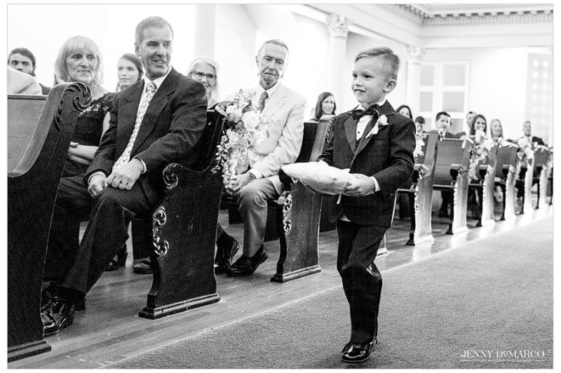 The ring bearer walks down the aisle as all of the guests smile at him.