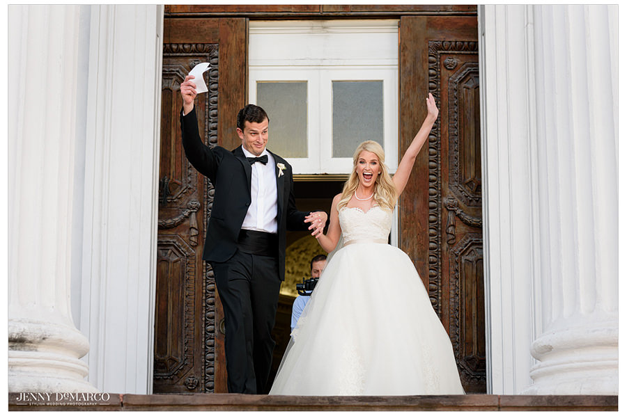 The couple raises their hand in celebration as they leave the church.
