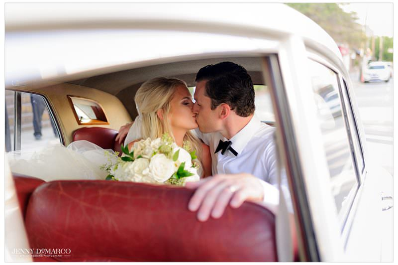 A cute photo of the couple kissing in a vintage white car with red leather seats.