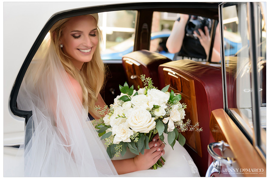 Solo shot of the bride sitting in a vintage car.