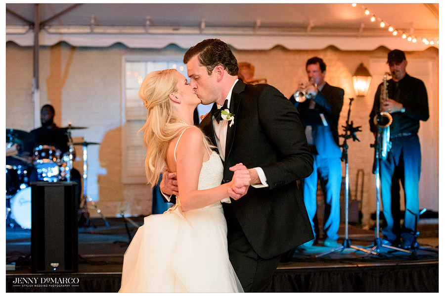 The couple shares a kiss on the dance floor in front of their guests.