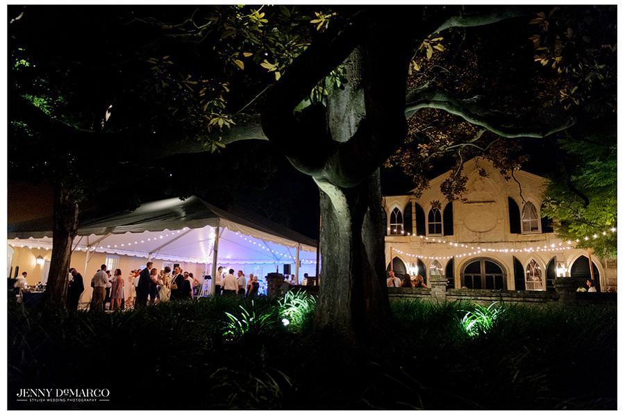 Wide angle shot of the dimly lit backyard reception and dance party.
