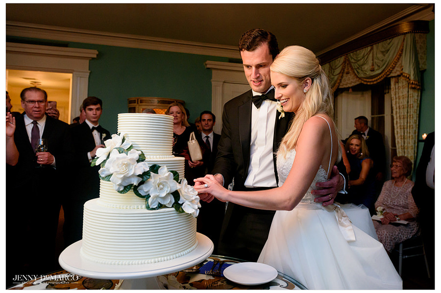 Bride and groom are hand in hand as they cut their all white wedding cake.