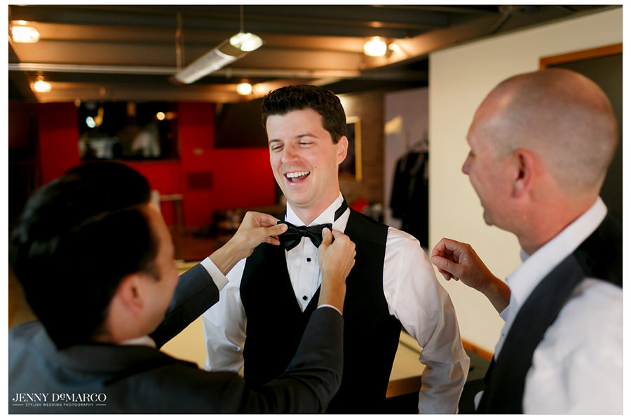 Groomsmen help the groom get ready.