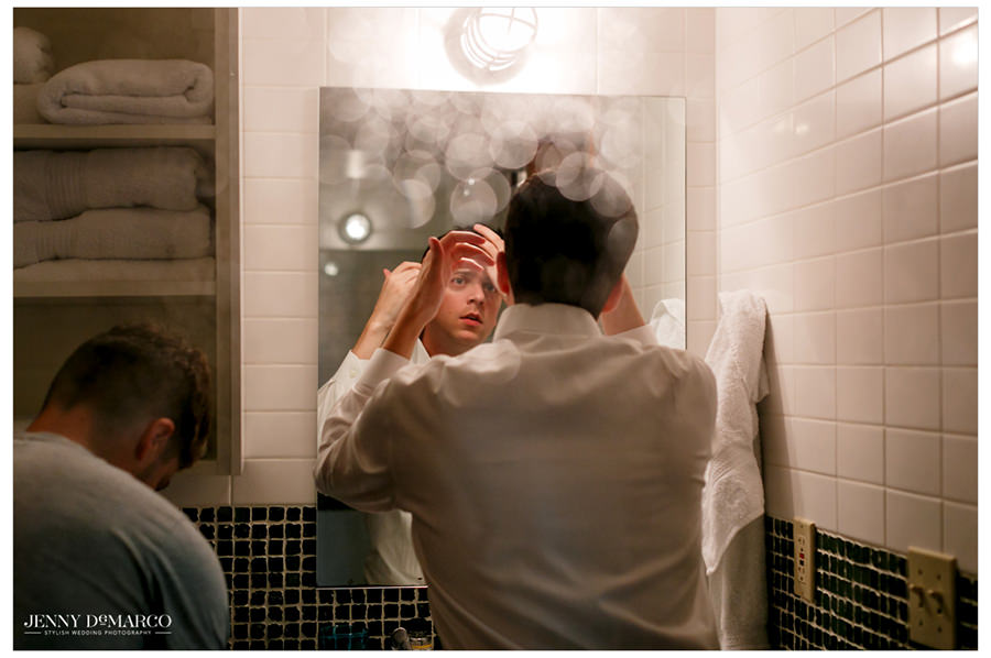 The groom fixes his hair in a bathroom mirror.