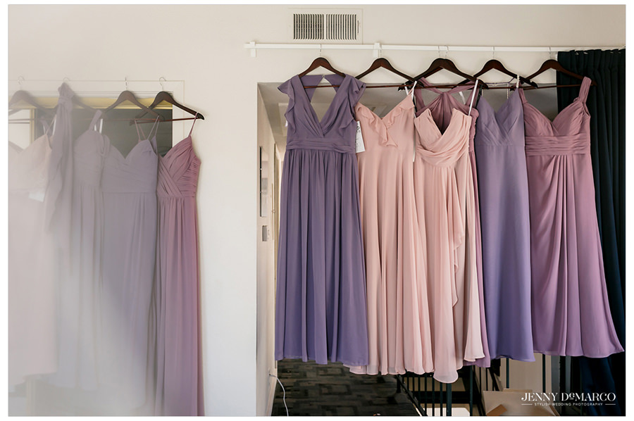 All of the bridesmaids purple-tones dresses hang on the wall.