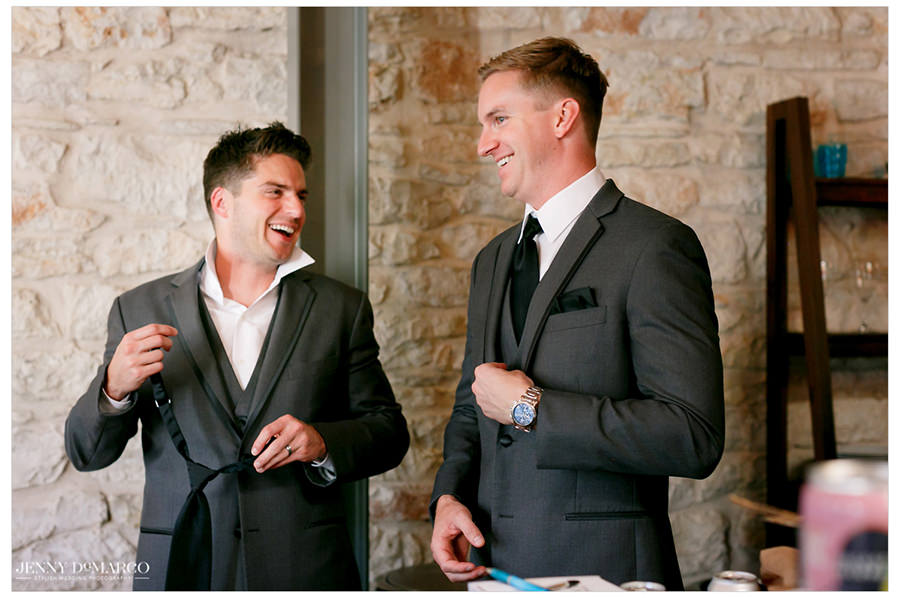 Groomsmen share a laugh as they get ready.