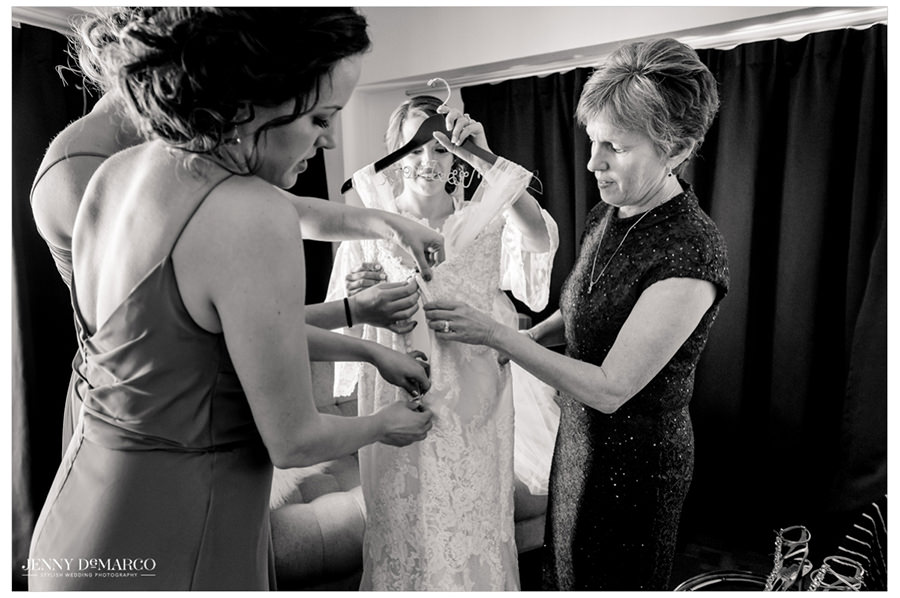 The brides closest people help prepare the wedding dress.
