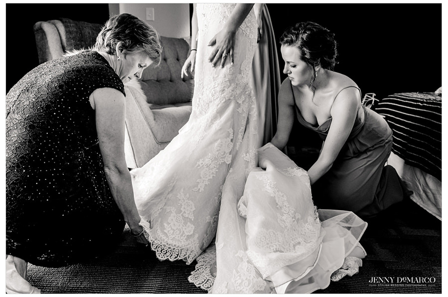 Mom and sister help fluff out the bride's floral gown.