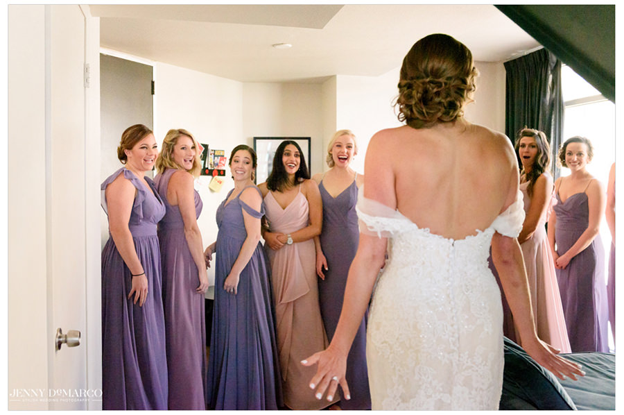 Bridesmaids look in wonder at the bride for the first time.