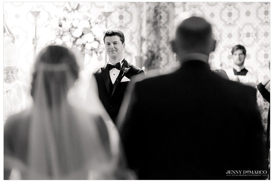 Groom looks longingly has his bride approaches.