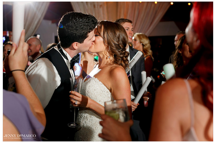 The couple shares a kiss in the middle of the crowded reception.
