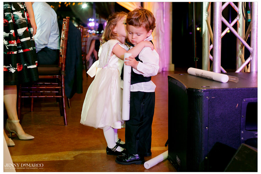 The ring bearer gets a kiss from the flower girl.