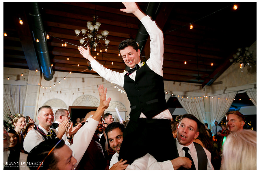 The groom is lifted high in the air by his buddies.